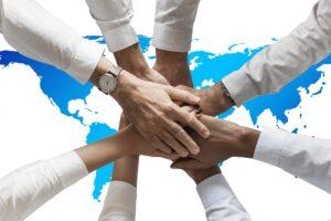 viele Hände zusammengestreckt über der Weltkarte